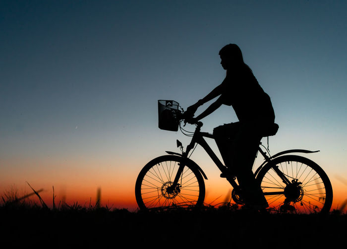 Silhouette man riding bicycle on field against sky during sunset