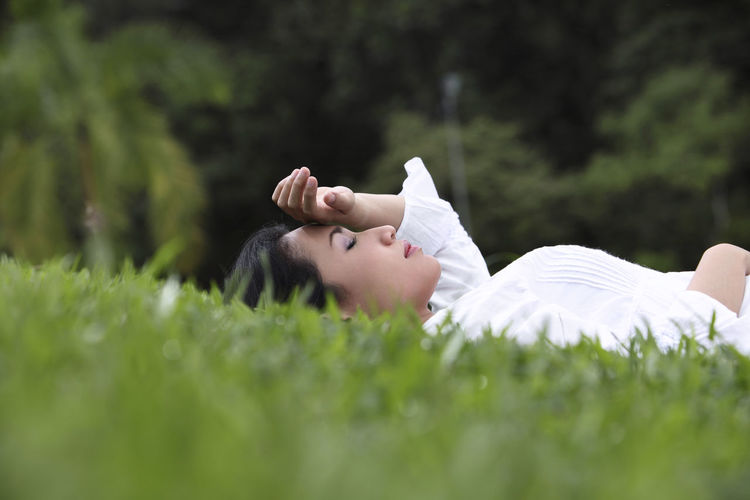 Woman lying on grassy field at park