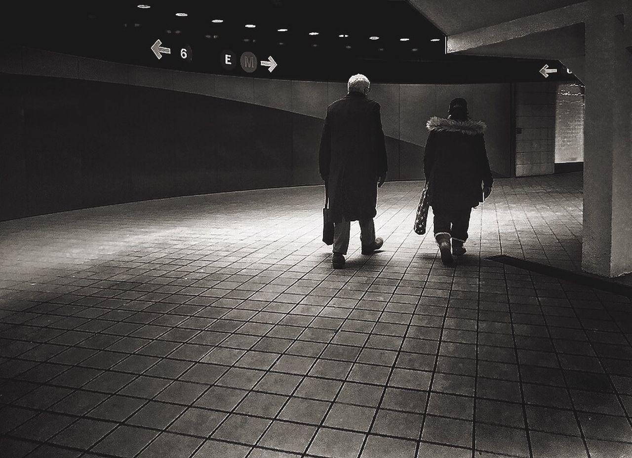 REAR VIEW OF TWO PEOPLE WALKING ON FOOTPATH
