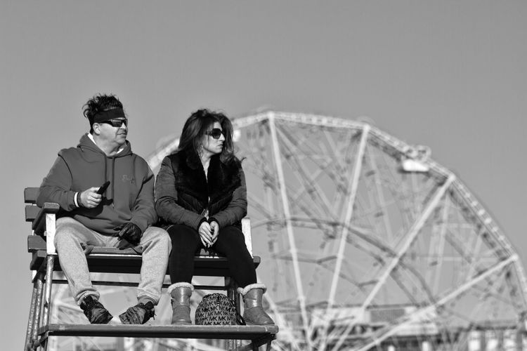 Two People Heterosexual Couple Real People Togetherness Ferris Wheel Outdoors Amusement Park Fairground Rides Funfair Lifeguard Stand Lifeguard Station Bench Black And White Black And White Photography Coney Island / Brooklyn NY Sitting Beach Photography Brooklyn Ny