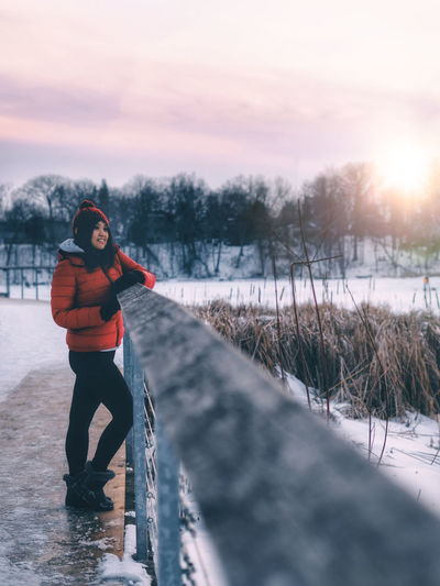 Woman standing in snow against sky during sunset