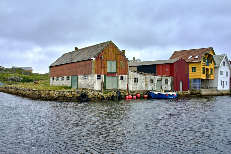Norway, Utsira, Nordvik: wooden houses overlooking the water basin Body Of Water Wooden Cloudy Day Outdoors Horizontal Warehouse Water Built Structure Building Exterior Architecture Sky Waterfront Cloud - Sky Building Mode Of Transportation Nautical Vessel Transportation Nature River House No People Rippled