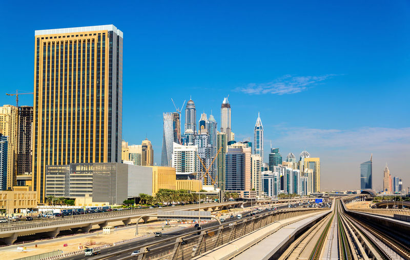 Modern buildings in city against blue sky