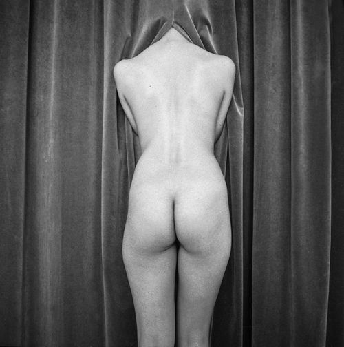 Rear view of shirtless woman standing against curtain