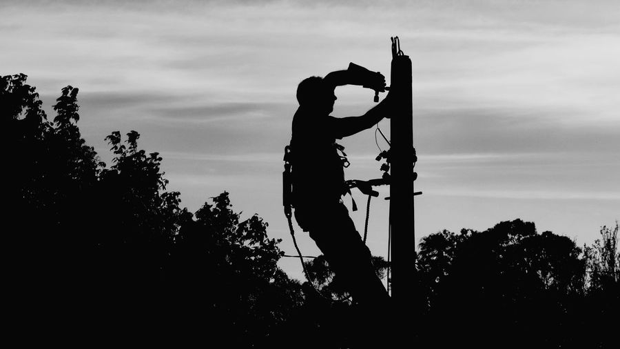 Silhouette One Man Only Only Men People Activity One Person Outdoors Sky Tree Electricity Pylon Man Working Adults Only Street Photography The Street Photographer - 2017 EyeEm Awards Monochrome Photography Black And White Collection  People_bw Electric Pole Man Working Out Electrical Equipment