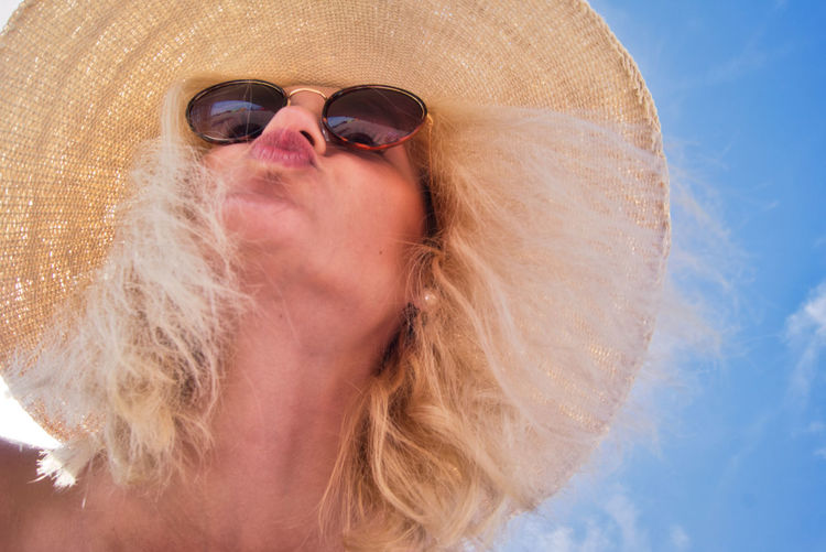 Low angle view of young woman wearing sunglasses against sky