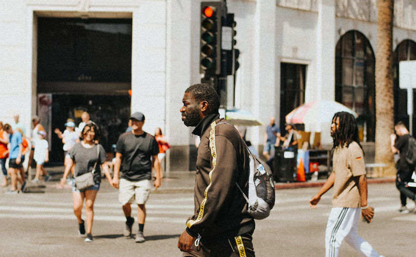 Group of people walking on road in city