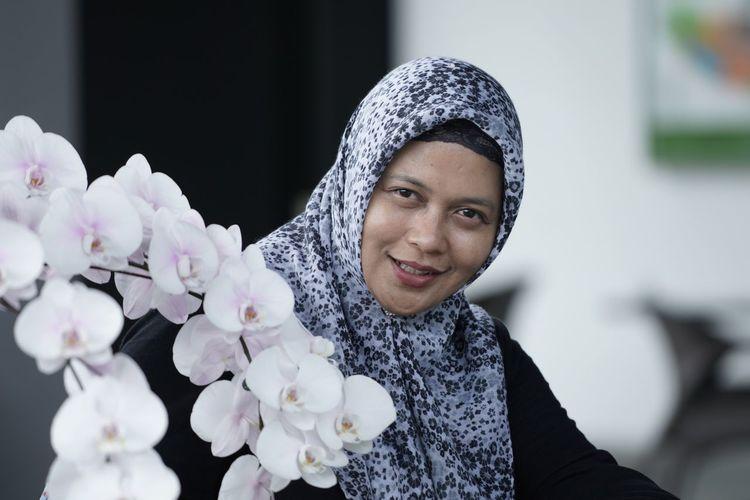 Portrait of woman wearing hijab by flowers
