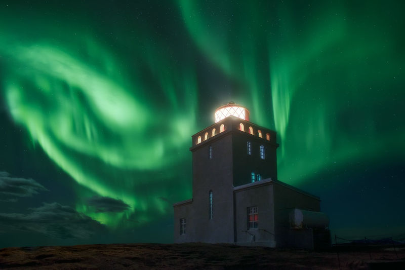 A lighthouse in Iceland under the borealis Northern Lights Night Illuminated Sky Building Exterior Scenics - Nature No People Astronomy Dramatic Sky Aurora Polaris Lighthouse Cloud - Sky Power In Nature Green Color Beauty In Nature Star - Space Iceland Vik Travel Winter