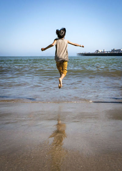 elevated Beach Beauty In Nature Clear Sky Day Energetic Full Length Jumping Leisure Activity Lifestyles Men Nature One Person Outdoors People Real People Sand Sea Sky Vacations Water Young Adult