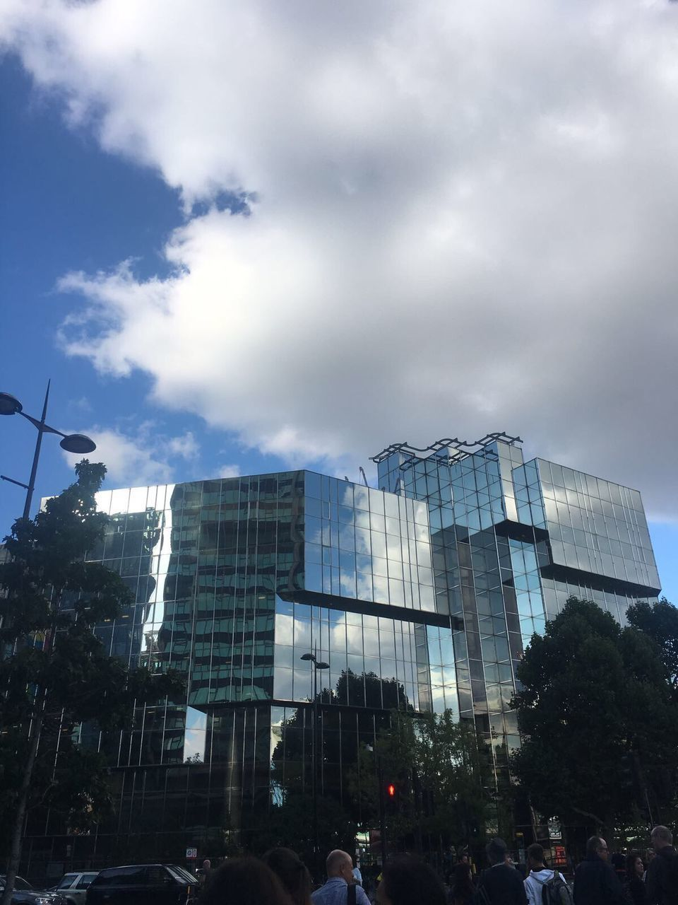 architecture, built structure, sky, building exterior, cloud - sky, modern, low angle view, day, large group of people, outdoors, skyscraper, tree, city, people