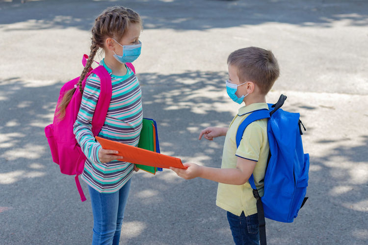 Back to school. brother and sister or boy and girl wearing protective medical masks