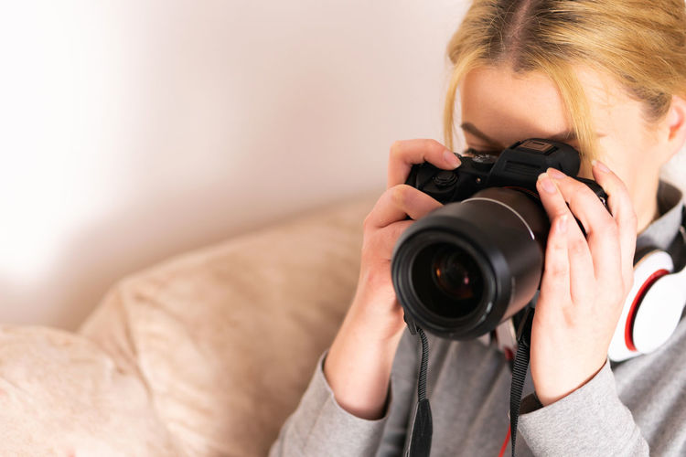 Photography Themes Camera - Photographic Equipment Photographing One Person Activity Technology Photographic Equipment Holding Digital Camera Indoors  Real People Women Camera Lifestyles Leisure Activity Focus On Foreground Occupation Adult Front View Photographer SLR Camera Modern Digital Single-lens Reflex Camera