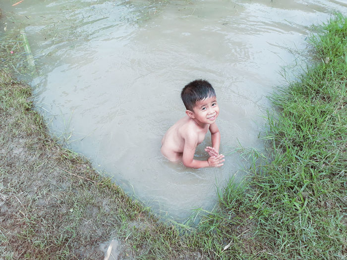High angle view of shirtless boy in water