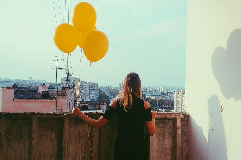 Rear view of woman holding balloons on balcony