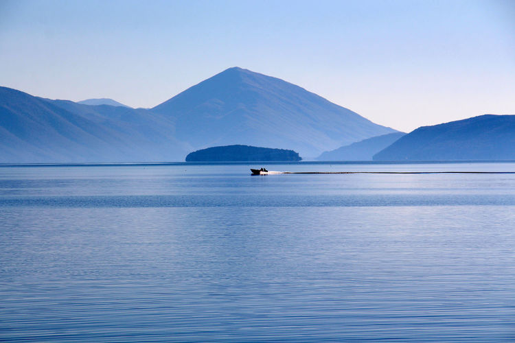 Distant view of boat sailing on lake against mountains