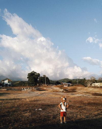Boy wearing lion headwear while standing on field against sky