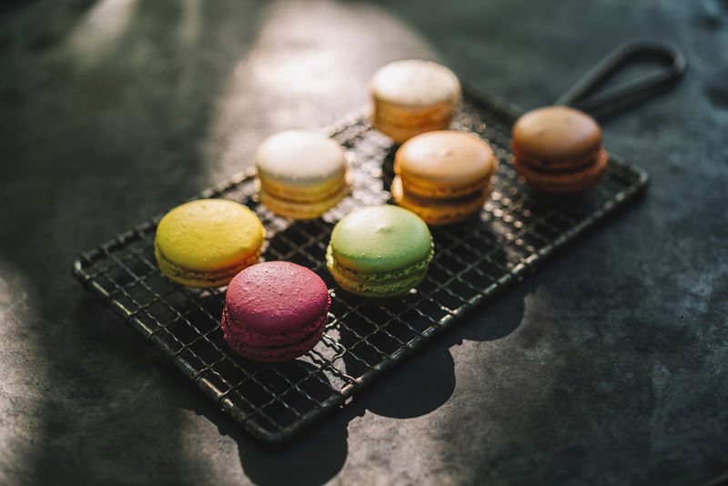 macaron or macaroon cakes in different colors on a grid Belgium Colors Cookies Dessert France Green Grid Macaroons Paris Pink Sugar Biscuit Time Candy Colorful Confectionery Flavor Food French Macaron Many Pastry Sandwitch Sweet Sweet Food Tasty