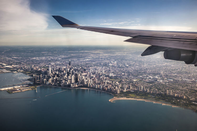 Cropped image of airplane wing flying over lake