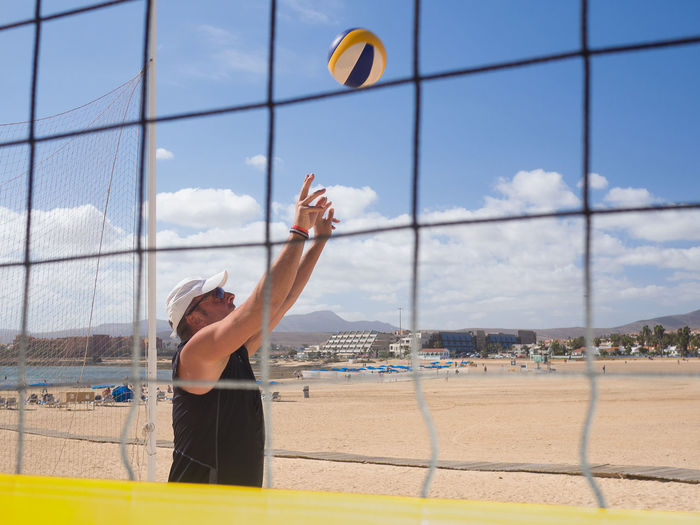 Man playing volleyball at beach against sky