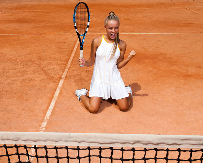 A young woman in a white tennis suit enjoys victory sitting on her knees on the court Holding Young Women Adult Front View Ball Motion Playing Tennis Net Clothing Young Adult Women Tennis Ball One Person Court Sport Tennis Racket Racket Tennis