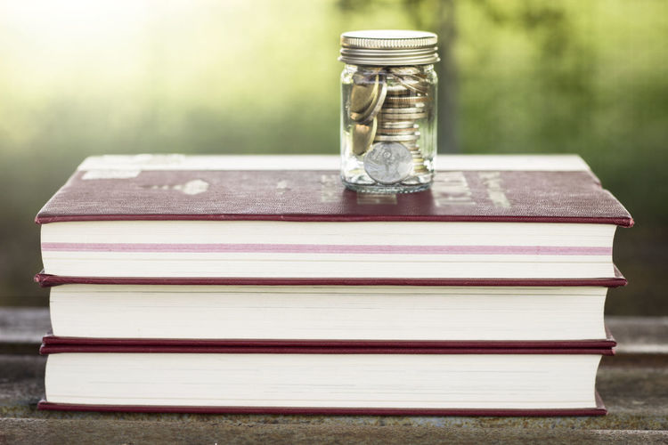 Close-Up Of Coins In Jar Over Books On Table
