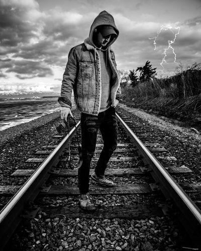 Man Holding Camera While Standing On Railroad Track Against Sky