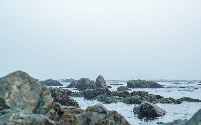 Rocks on beach against foggy sky