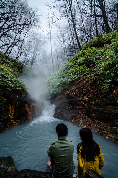 Noboribetsu, Japan- 15 NOV 2017: Beautiful couple soaking their leg in the natural footbath at the Oyunuma River, a hot spring river that flows from Lake Oyunuma, near hell valley, Noboribetsu Couple Hokkaido Noboribetsu Onsen Beauty In Nature Cute Day Foot Bath Hot Spring Leisure Activity Lifestyles Men Motion Nature Outdoors Oyunuma Real People Rear View River Scenics Togetherness Water Waterfall Women