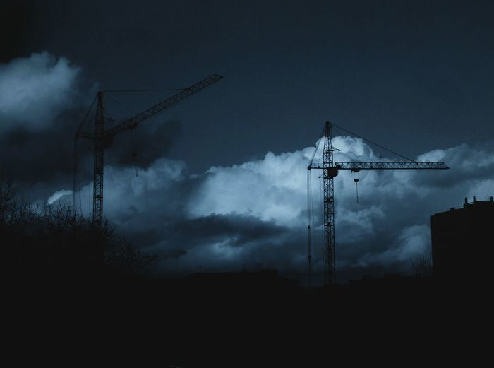 Low Angle View Of Silhouette Crane Against Cloudy Sky At Dusk