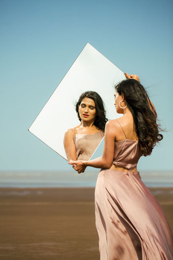 Woman holding mirror at beach against sky