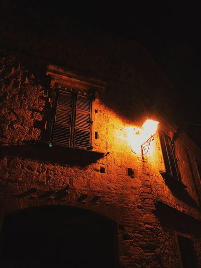 Night scene, old Italian building. Darkness And Light Italian Architecture Night Night Lights Old Building  Shutters Stone Building Stone Masonry Wall Lamp