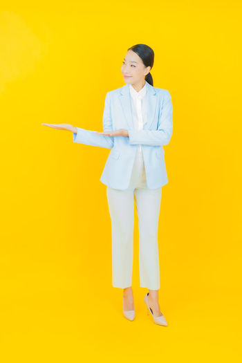 Full length of a woman standing against yellow background