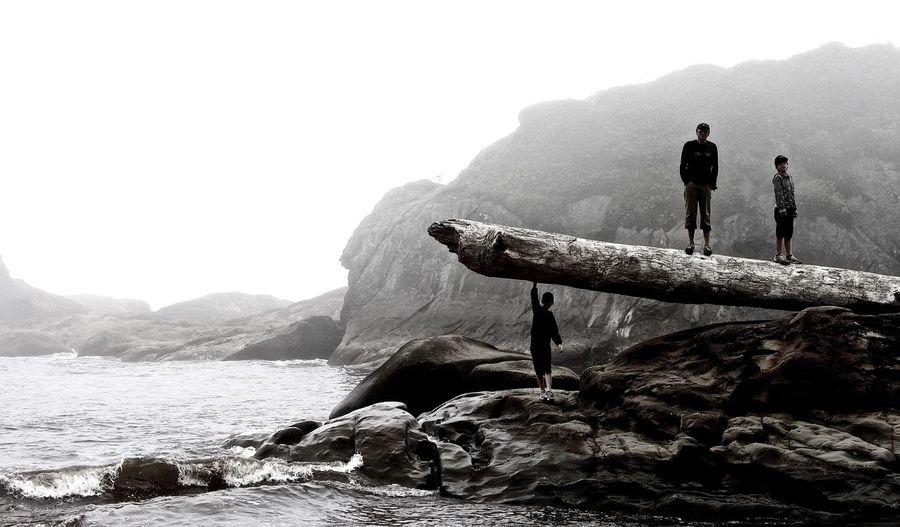 Three people standing on rocky coastline
