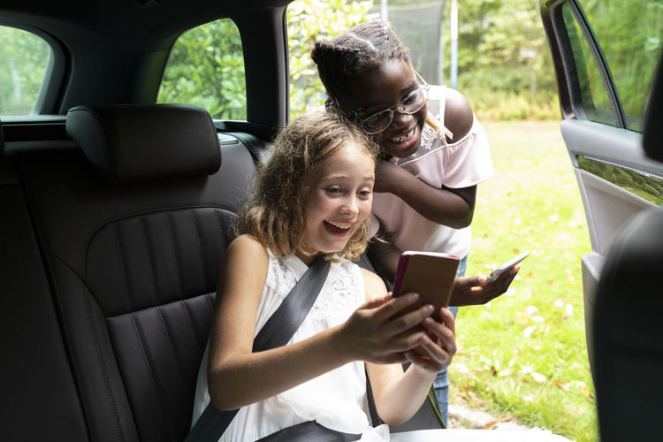 Young woman using phone while sitting in car