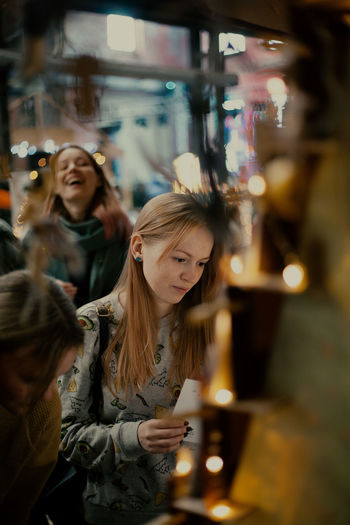 Portrait of young woman looking at illuminated shop