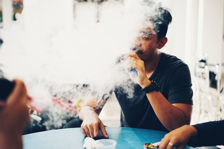 Young man smoking electronic cigarette while sitting at table