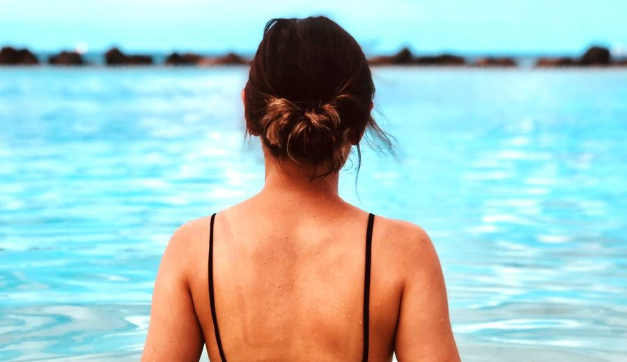 Rear view of woman looking at swimming pool