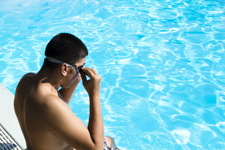 High angle view of shirtless man wearing goggles while sitting by pool