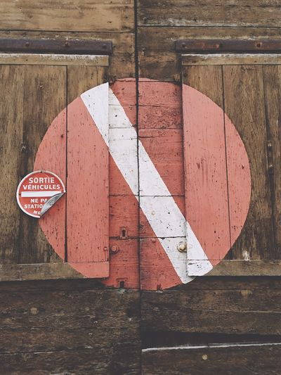 Low angle view of symbol on wooden wall