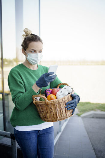 Woman using smart phone while holding basket outdoors