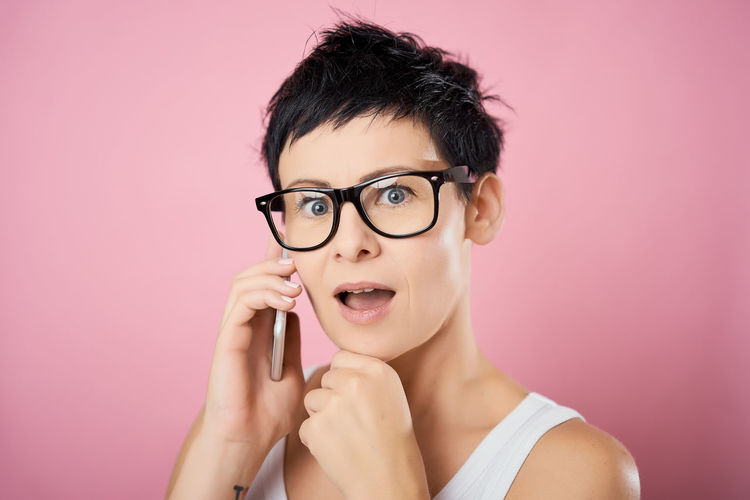 Colored Background Portrait Studio Shot Headshot Glasses Eyeglasses  One Person Pink Background Looking At Camera Young Adult Indoors  Front View Pink Color Adult Holding Beautiful Woman Beauty Women Hairstyle Human Face
