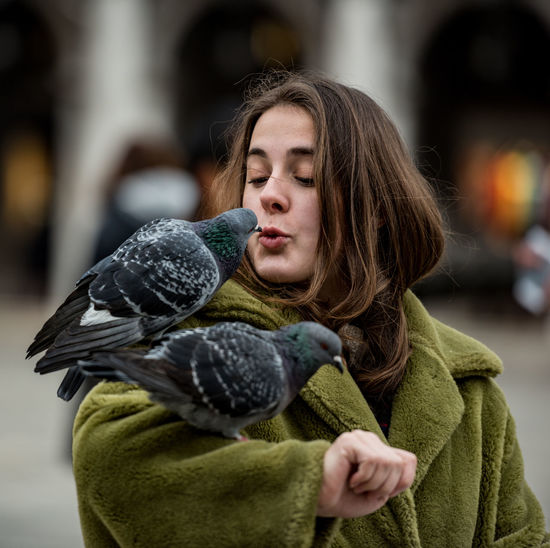Close-up of young woman with bird