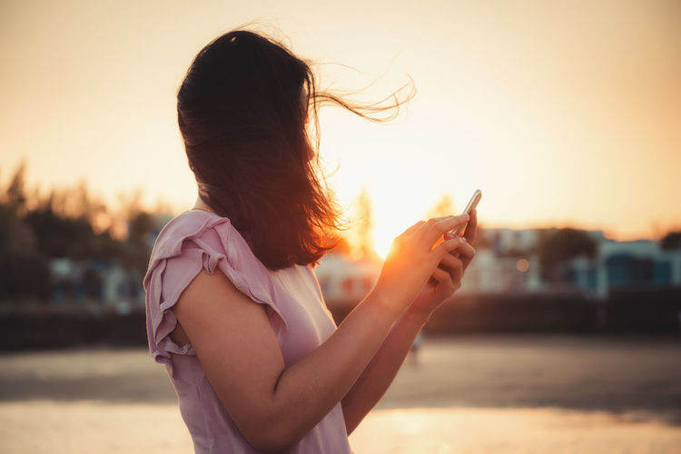 Side view of mid adult woman using smart phone while standing against sky during sunset