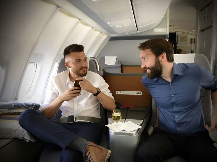 Young Men Talking While Traveling In Airplane