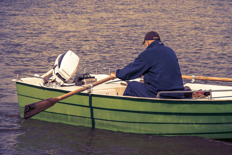 Rear view of man sitting on boat moored in sea