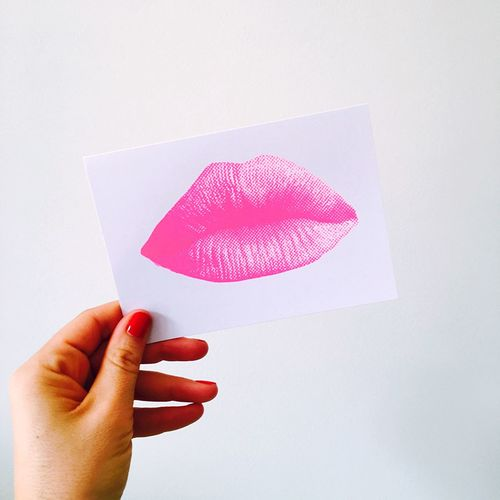Close-Up Of Hand Holding Paper With Lipstick Kiss Against White Background