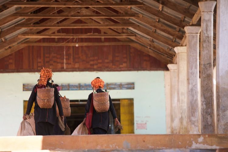 Rear View Of Women Carrying Baskets In Building