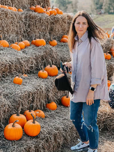 High angle view of woman standing by pumpkins