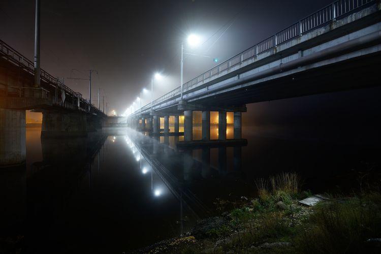 Train on illuminated bridge at night